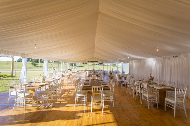 The Grand Pavilion set with rustic timber tables and white tiffany chairs